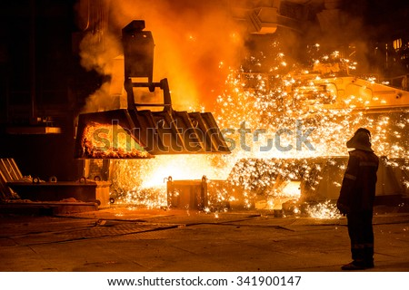 Steelworker near a blast furnace with sparks - stock photo