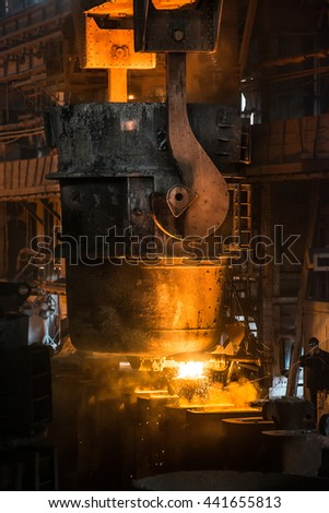 Steelworker pours liquid metal into molds from tank - stock photo