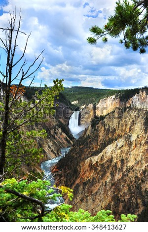 "Steep canyon walls frame the Yellowstone River in ""The Grand Canyon of the Yellowstone,"" in Yellowstone National Park.  Lower Falls and large white clouds are at back  - stock photo"