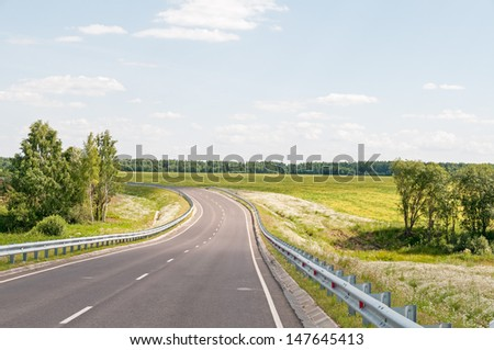 Steep highway turn with metal rails along against blossoming meadow and forest background. Kaluzhsky region, Russia.  - stock photo