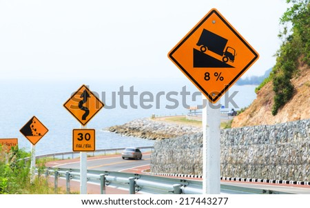 Steep Hill Descent Signs with Scenery along The Beach Road - stock photo