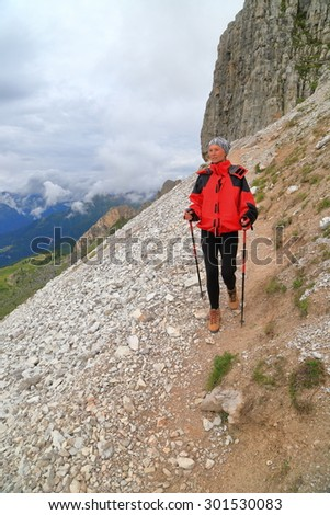 Steep mountain slope and hiker descending a rocky trail in overcast weather, Dolomite Alps, Italy - stock photo