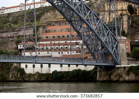 Steep River Banks. The Dom Luis Bridge spans the divide caused by the fast flowing Douro River in Porto, Portugal. Through the bridge are warehouses that cascade down the steep river valley banks.  - stock photo