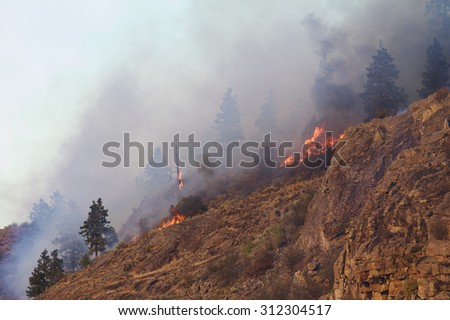 Steep rocky cliff burns during the 2015 Okanogan Complex Wild Fire, the largest, most destructive forest fire in Washington State history - stock photo
