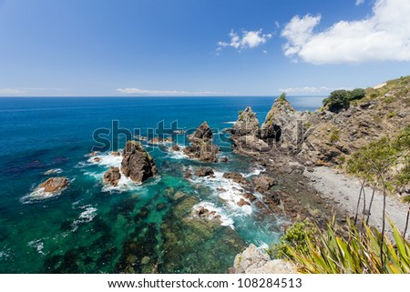 Steep rocky coastal cliffs on tip of Tawharanui peninsula, North Island of New Zealand - stock photo