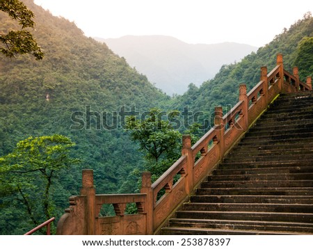 Steep stairs in the forest leading to summit of Mount Emei, Emeishan, Sichuan, China  - stock photo