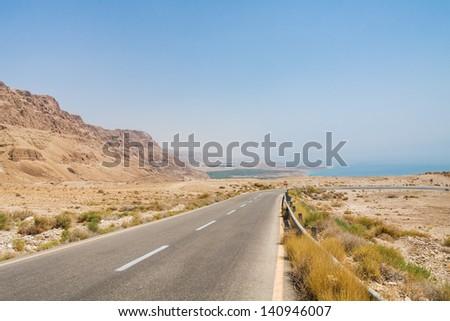 Steep turn of descend highway in Judean desert with Dead Sea in background. Metzoke Dragot, Israel. - stock photo