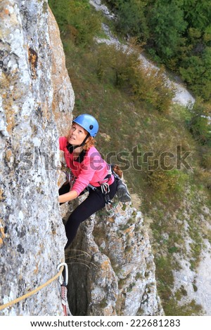 Steep wall and woman climber hanging high above ground - stock photo