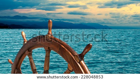 Steering wheel at sea background.  Skipper's wheel on an old ship. Sea voyage at the seaside with captains wheel of the old vessel, closeup. - stock photo