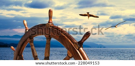 Steering wheel at sea background.  Skipper's wheel on an old ship. Sea voyage at the seaside with captains wheel of the old vessel, closeup. Marine skyline on the sundown with two seagull on the sky. - stock photo
