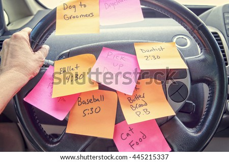 Steering wheel covered in notes as a reminder of errands to do - stock photo