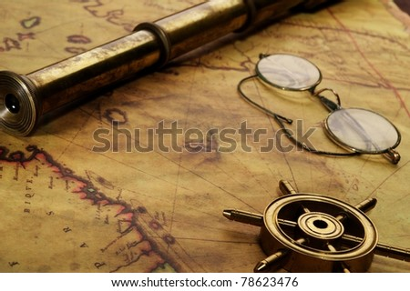 Steering wheel, glasses and spyglass on the old map - stock photo