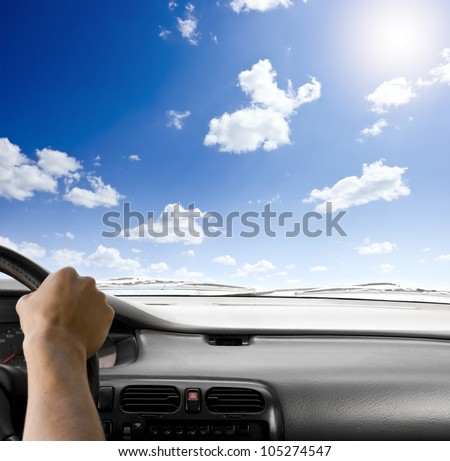 Steering wheel of a car and sky background - stock photo