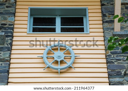 steering wheel of a ship on a facade of a house - stock photo