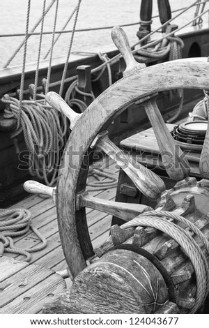 Steering wheel of an ancient sailing vessel, black and white photo - stock photo