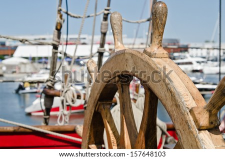 Steering wheel of an old sailing vessel, close up - stock photo