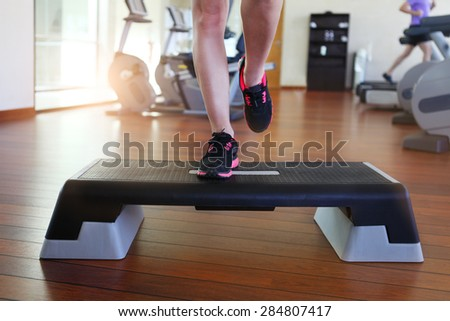 Step aerobics. Cropped image of beautiful young woman doing step aerobics while in health club - stock photo