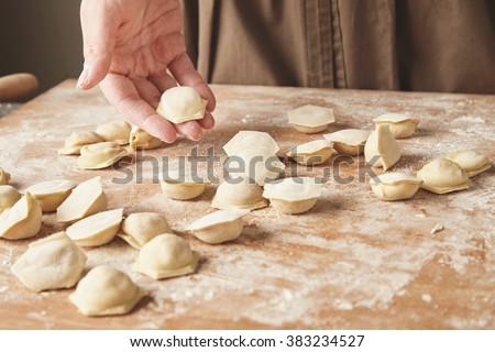 Step by step process of making home-made dumplings, ravioli or pelmeni with minced meat filling using ravioli mold or ravioli maker. Ready for cooking raviolis on wooden board, woman hand holds one - stock photo