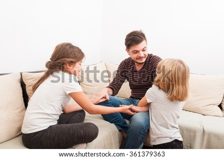 Stepfather having fun with step daughters on the couch or sofa - stock photo