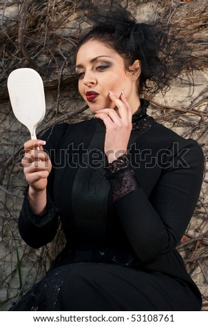 stepmother looks into the mirror - stock photo