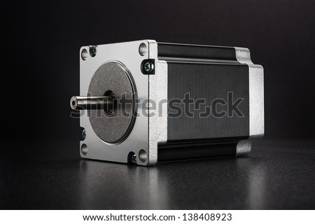 Stepper motor with NEMA standard flange, used for driving linear axes of CNC machines like 3D printers and routers, on dark background with diffused reflection - stock photo