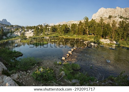 stepping stones on a trail across a stream in the Sierra Nevada Mountains - stock photo