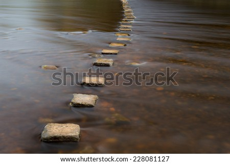 Stepping stones over a river. - stock photo