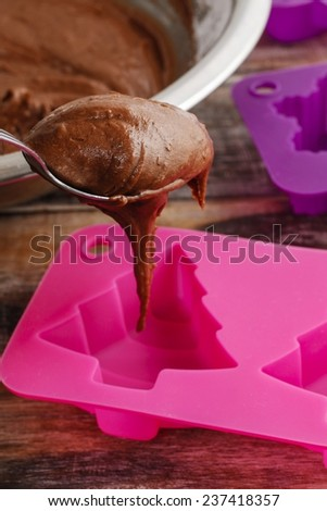 Steps of making chocolate cake: filling silicone mold with pastry - stock photo