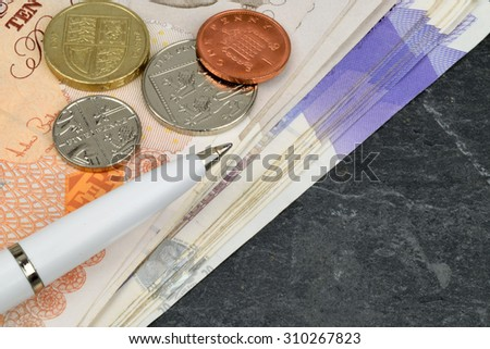 Sterling Currency notes, coins and pen, on slate. - stock photo