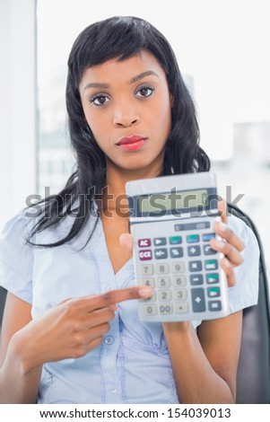 Stern businesswoman holding a calculator in office - stock photo