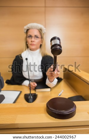 Stern judge banging her hammer in the court room - stock photo