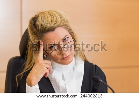Stern judge looking at camera in the court room - stock photo