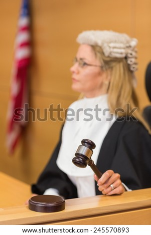 Stern judge sitting and listening in the court room - stock photo