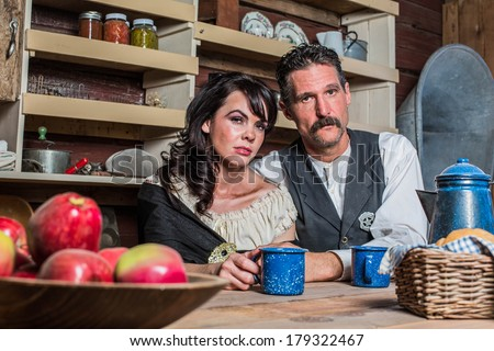 Stern looking western sheriff and woman pose inside of a house - stock photo