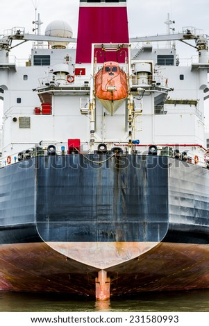 Stern of a container ship with orange life raft - stock photo