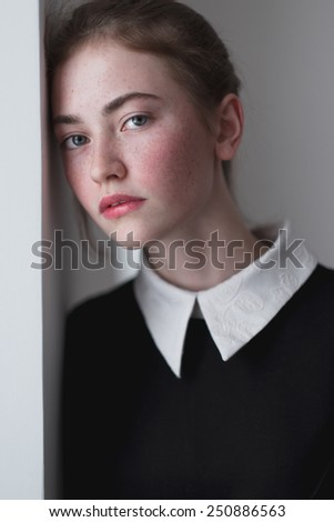stern portrait of a beautiful young girl with freckles - stock photo