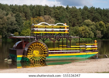 Sternwheeler moored on river strand attraction waiting for tourists, yellow-green old paddle wheeler, steamer or steamboat-like riverboat named Katamaran on Bug River in Poland. - stock photo