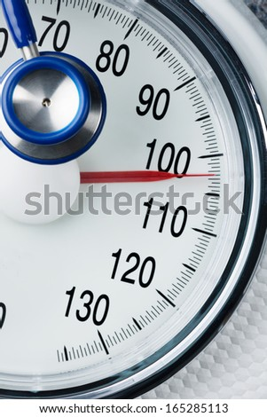 stethoscope and balance, symbol photo for weight, diet and heart disease - stock photo