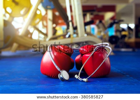 Stethoscope and boxing gloves on a Blue wall fitness center - stock photo
