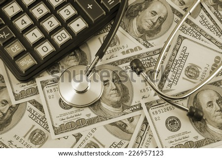 Stethoscope and calculator on banknotes, cost of healthcare concept  - stock photo