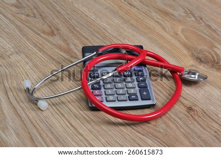 Stethoscope and calculator on table. - stock photo