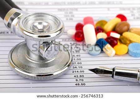 Stethoscope and colourful pills over medical record - stock photo