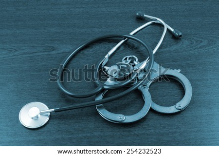 Stethoscope and handcuffs on table - stock photo