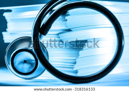 Stethoscope and heap of paper cards in toning - stock photo