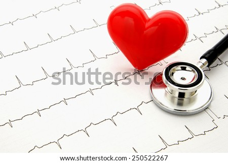 Stethoscope and heart object on electrocardiogram - stock photo