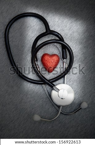 Stethoscope and heart symbol on a dark table with shadows - stock photo
