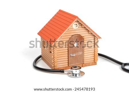 Stethoscope and Model House on white background - stock photo