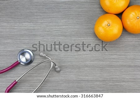 Stethoscope and orange on a wooden background. Medical equipment, Healthy food, Healthy eating concept. - stock photo