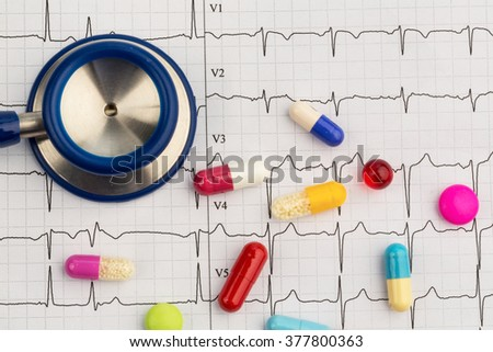 stethoscope and pills on an ekg - stock photo