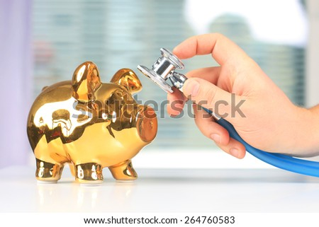 Stethoscope in hand and piggybank on white table.. - stock photo